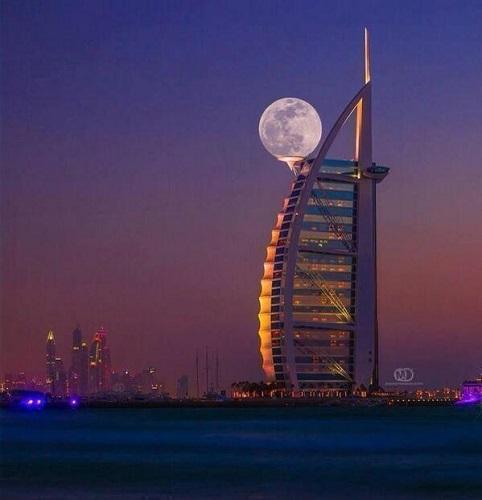 Increíble fotografía en Dubai con la luna apoyada en el rascacielos